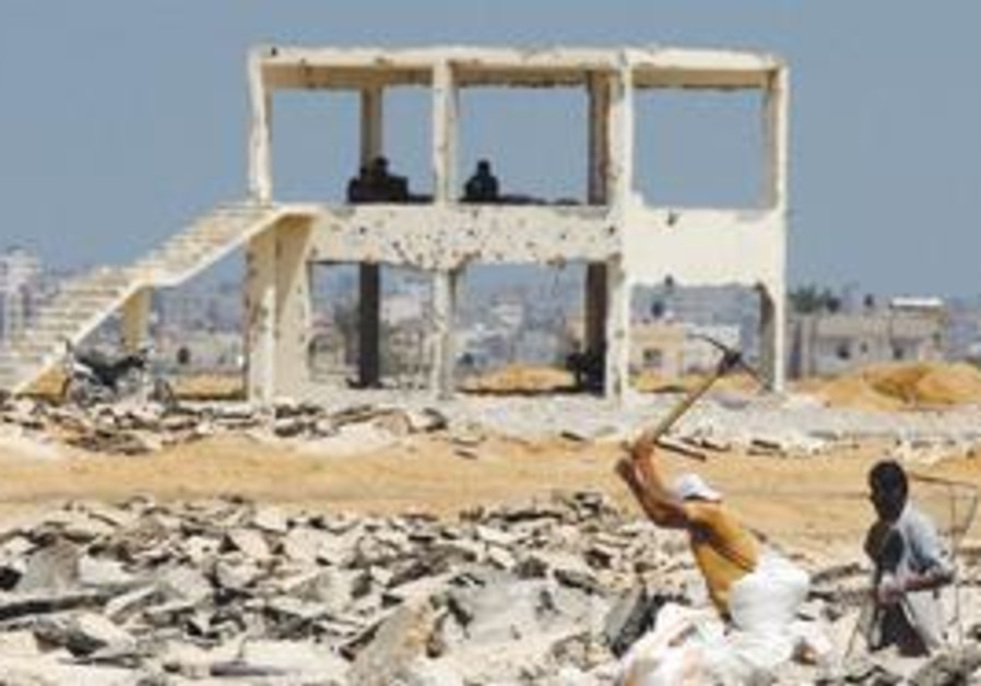 PALESTINIANS dig up gravel to be sold for construction, Monday, on the former runway of the bombed-o