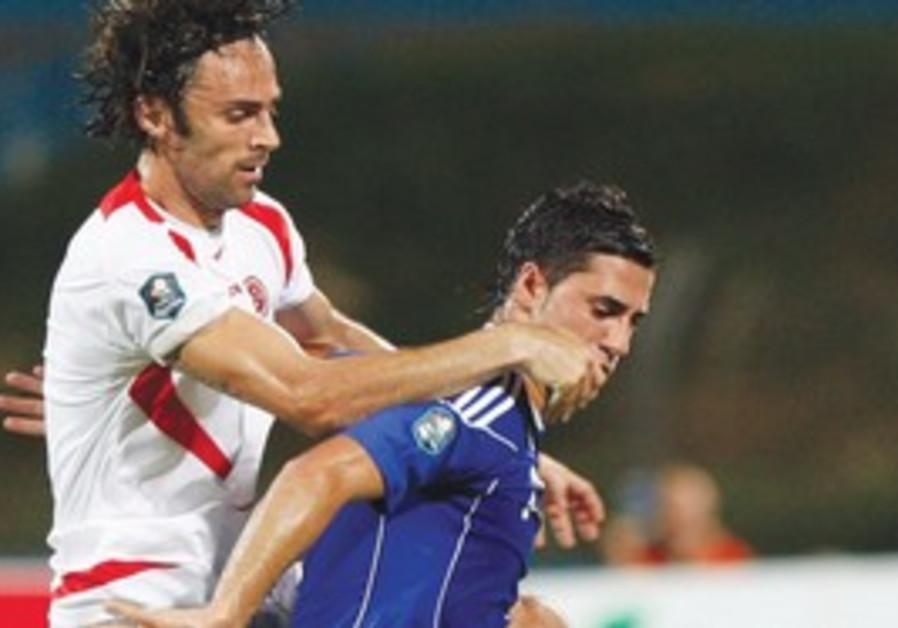 ISRAEL'S BIRAM KAYAL fends off a Malta player.