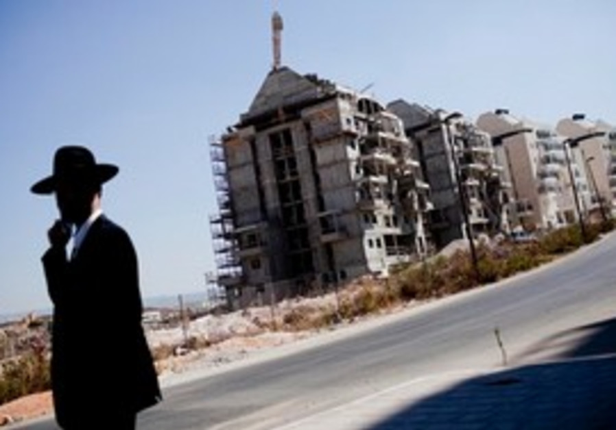 Settler walks near West Bank construction site