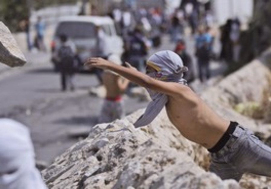 A MASKED Palestinian youth throws a rock