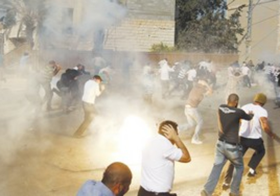 Rioters flee tear gas in the city of Umm el-Fahm