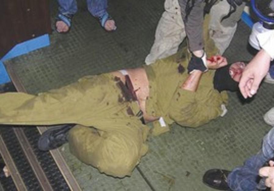 WOUNDED IDF soldier is surrounded by people