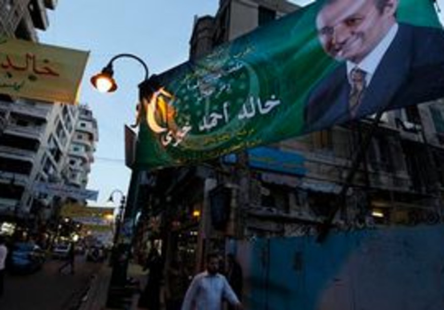 Egyptians walk by an electoral poster