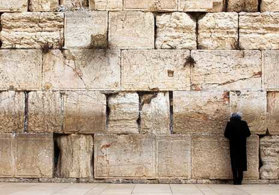 A man prays alone at the Kotel during the storm