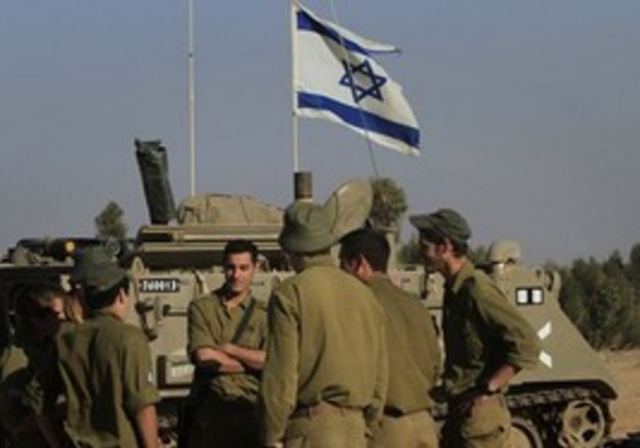 IDF troops standing by a tank on Gaza border