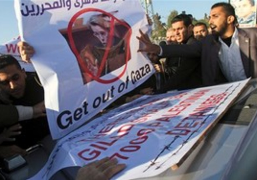 Palestinians block the vehicle carrying French FM