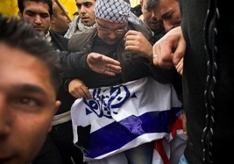 Palestinians destroy Al-Jazeera logos in rally