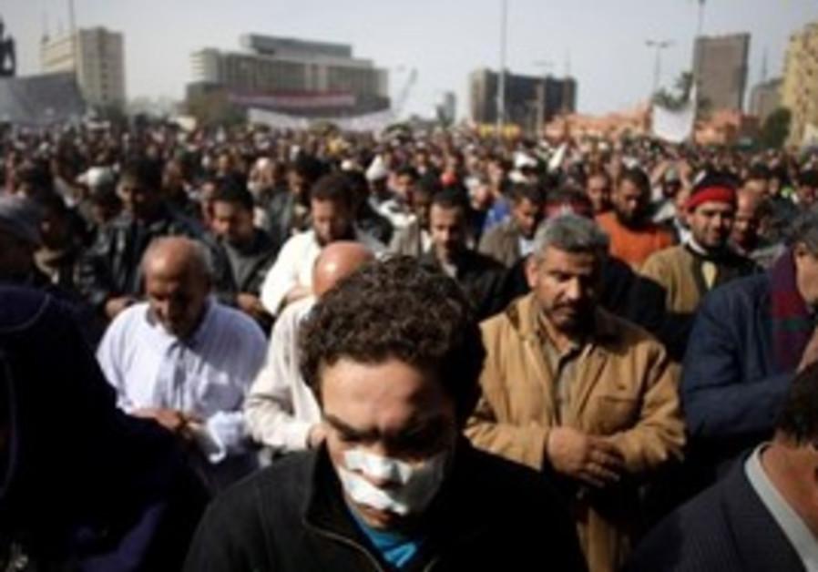 Anti-government protestors pray in Tahrir Square,