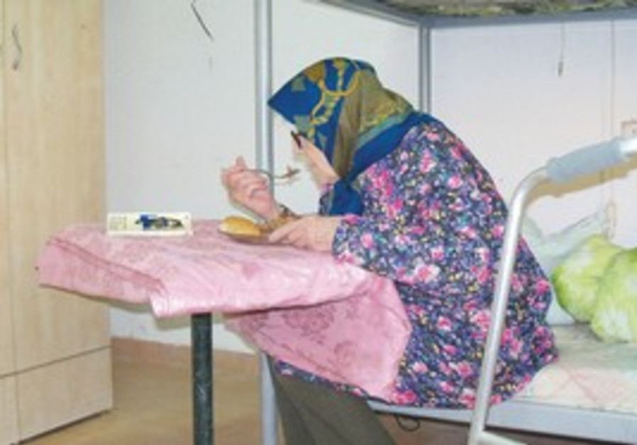 An elderly woman eats at the hostel