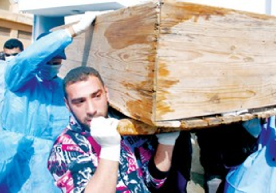 Men carry coffin at Al-Jalaa hospital in Benghazi