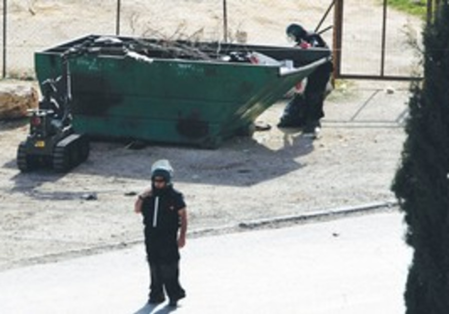 Police sappers inspecting trash dumpster
