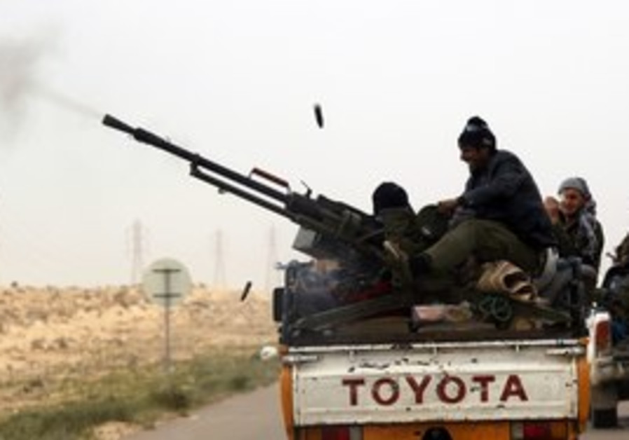 A rebel fires his anti-aircraft gun near Benghazi.