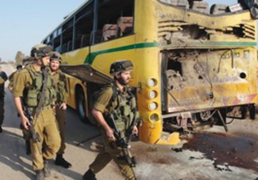 Soldiers walk by the school bus hit by a missile.
