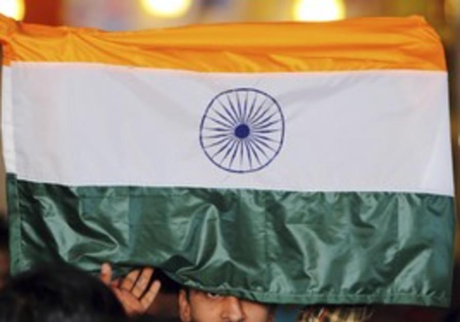 A man holds up an Indian flag.
