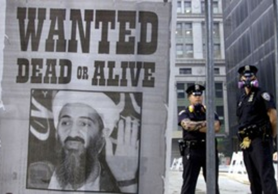 Police stand near a wanted poster of bin Laden