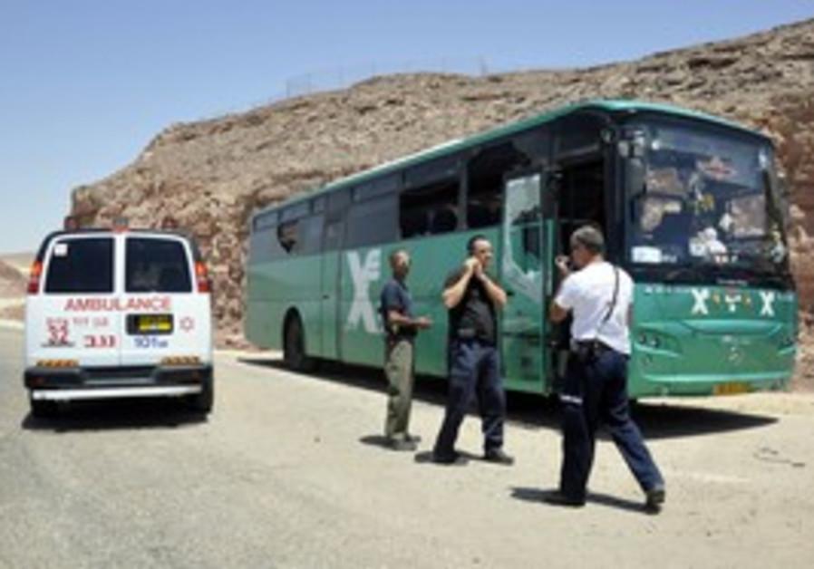 Security personnel next to bus after ambush, Thurs