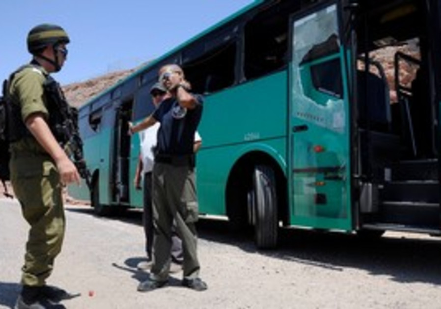 Security forces standing next to an attacked bus