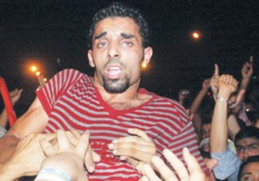 EGYPTIANS CARRY Ahmed al-Shahat on their shoulders