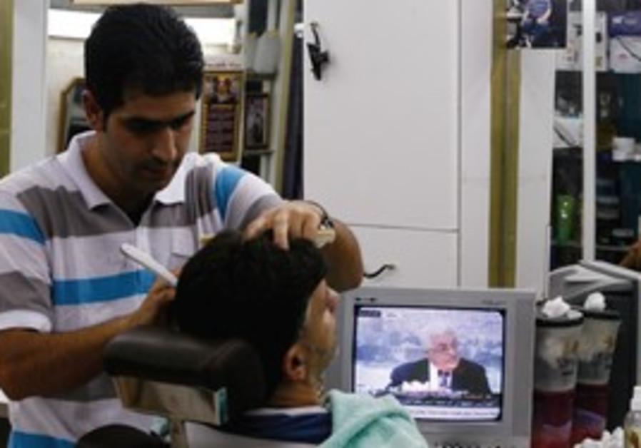 Palestinians in barber shop watch Mahmoud Abbas.