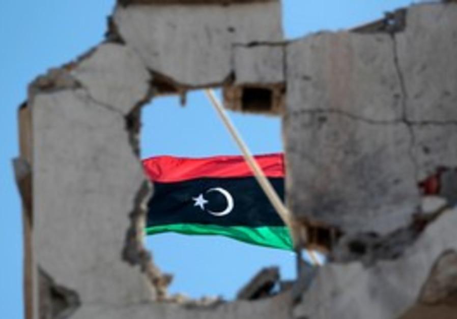 Libya flag seen on top of a damaged building