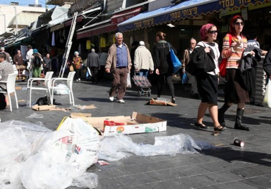 Pedestrians walk by debris neglected due to strike