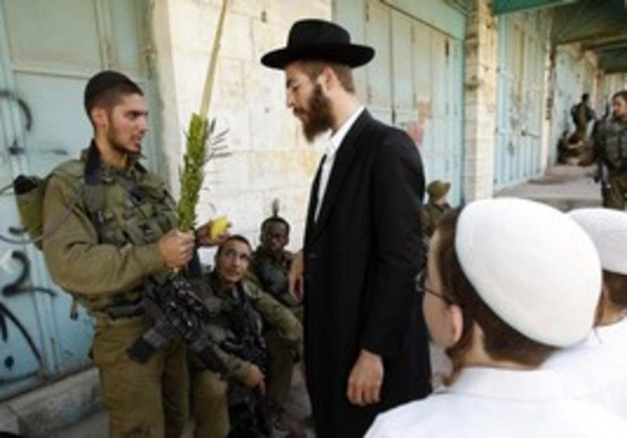 IDF soldier, religious Jews on sukkot, Hebron