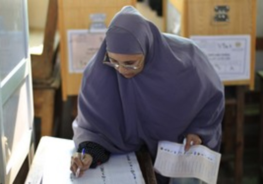 Egyptian woman reads a ballot paper before vote