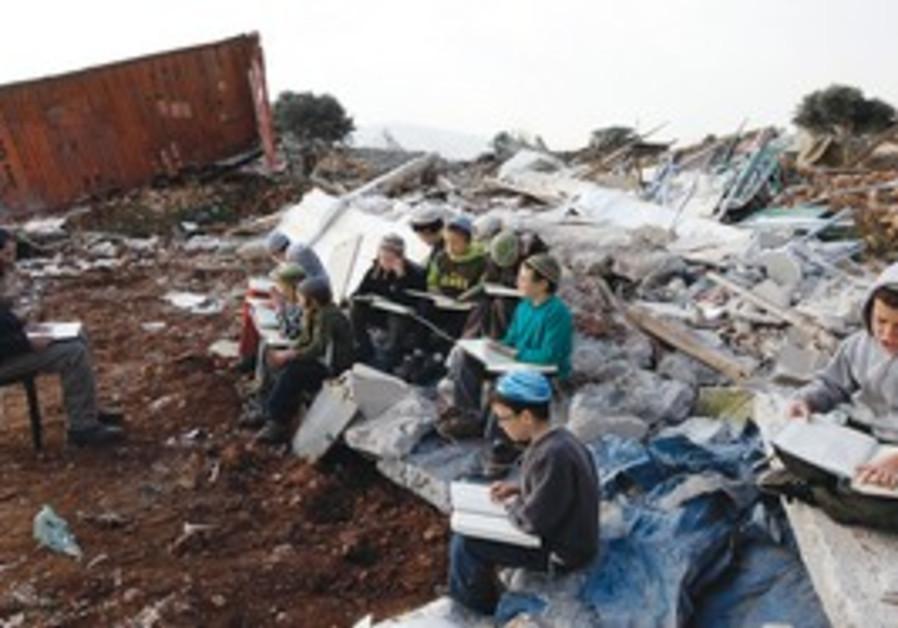 boy studies near destroyed home, Mitzpe Yitzhar