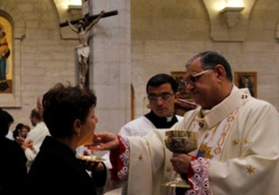 Latin Patriarch Twal gives communion in Bethlehem