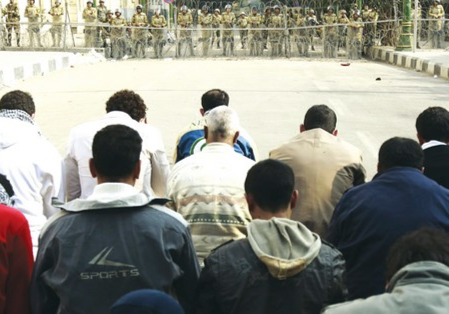 Muslims pray in front of soldiers, Egypt