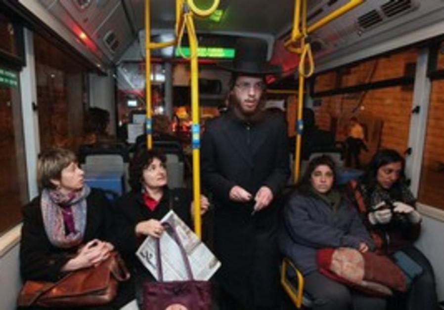 Haredi man passes women sitting in front of bus