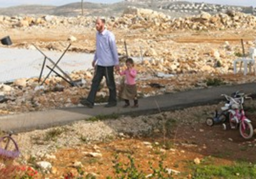 Migron residents walk by site of demolished home