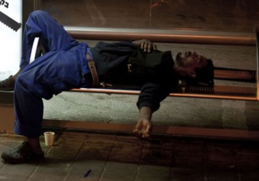 Homeless African migrant on bench in south TA