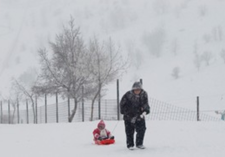 woman pulls a child on a sled on Mount Hermon