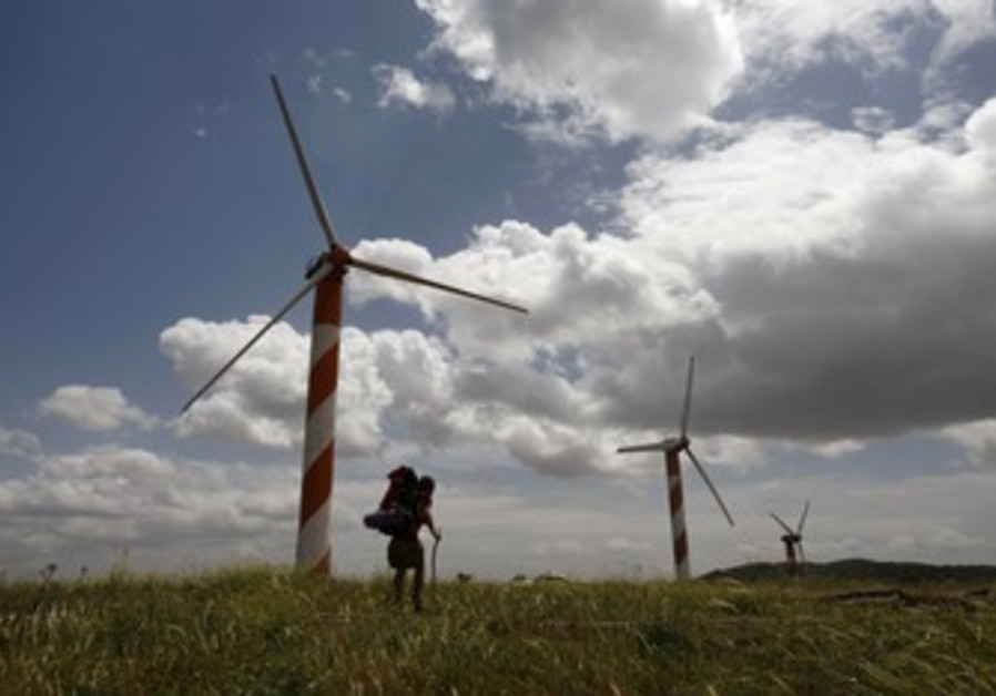Hiker walks past wind turbines in the Golan Height