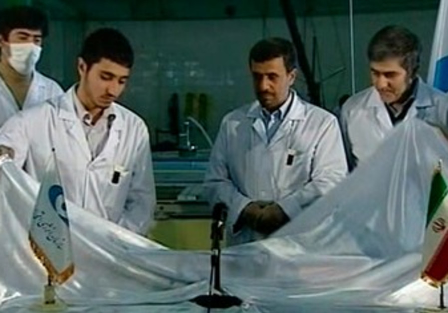 Ahmadinejad looks on next to nuclear scientists