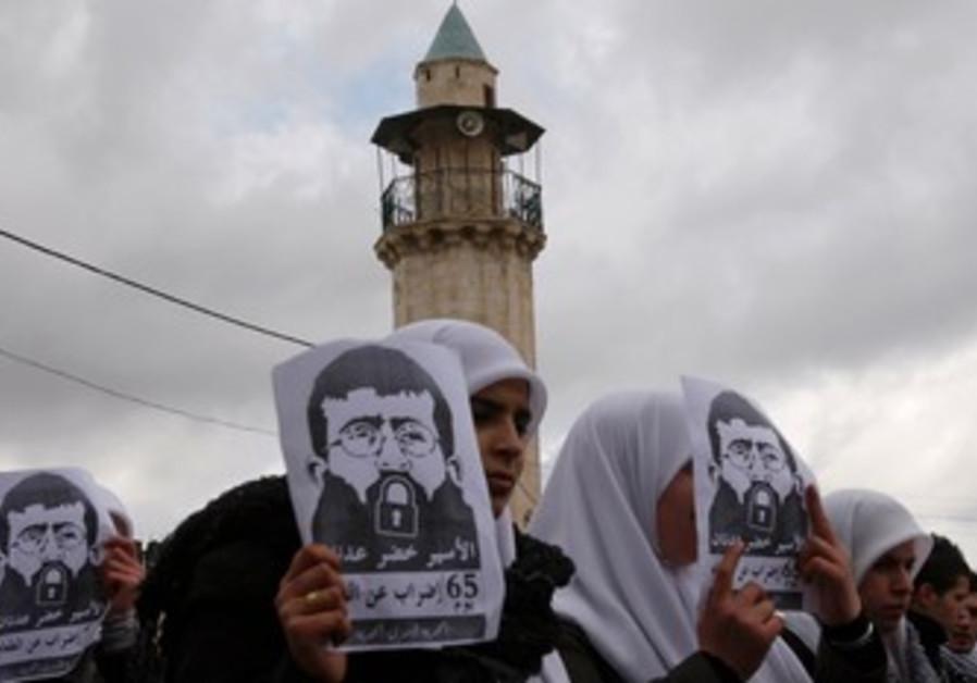 Palestinian students hold signs of Khader Adnan