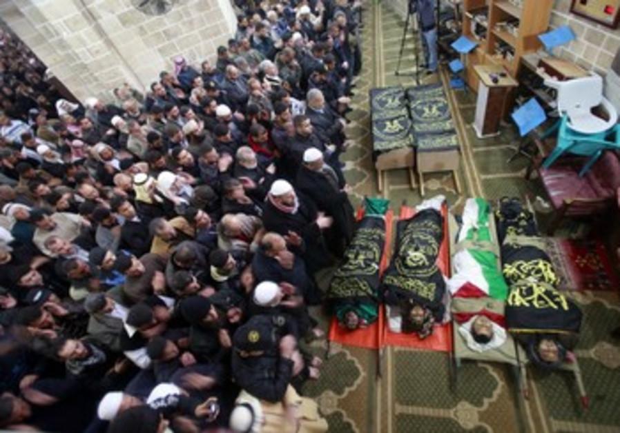 Palestinains pray near Islamic Jihad bodies