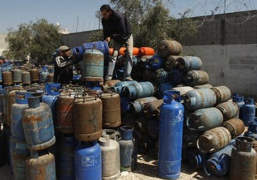 Gazans arrange gas cylinders at gas station