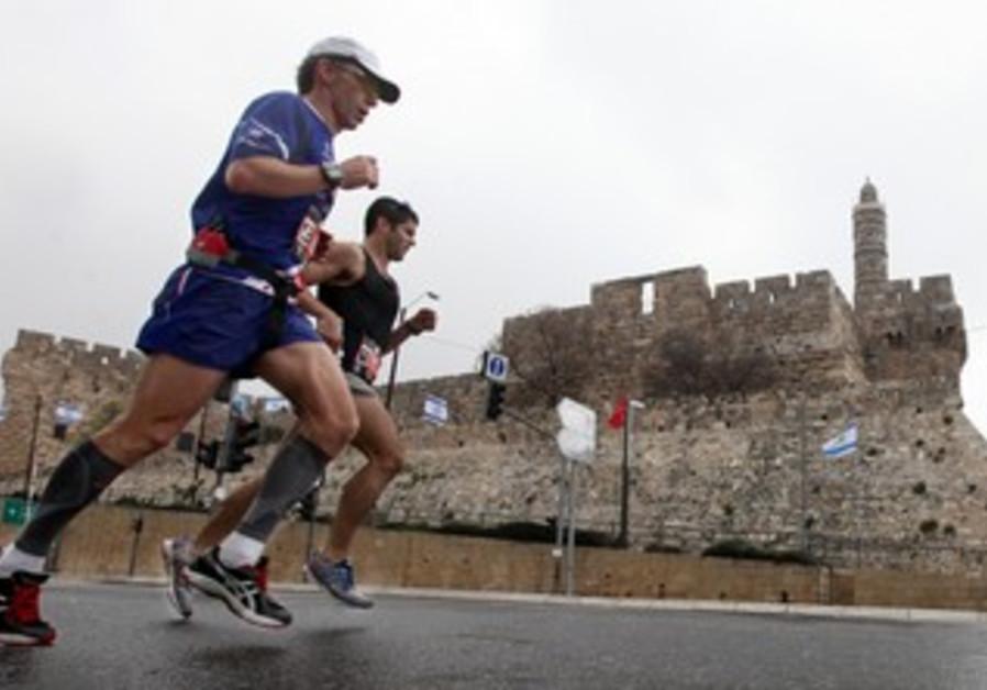 Runners in Jerusalem Marathon pass Old City