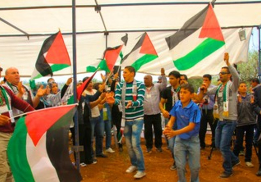 Palestinians hold flags at Bil'in Conference