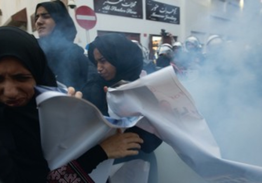Protesters in Manama react to sound grenade