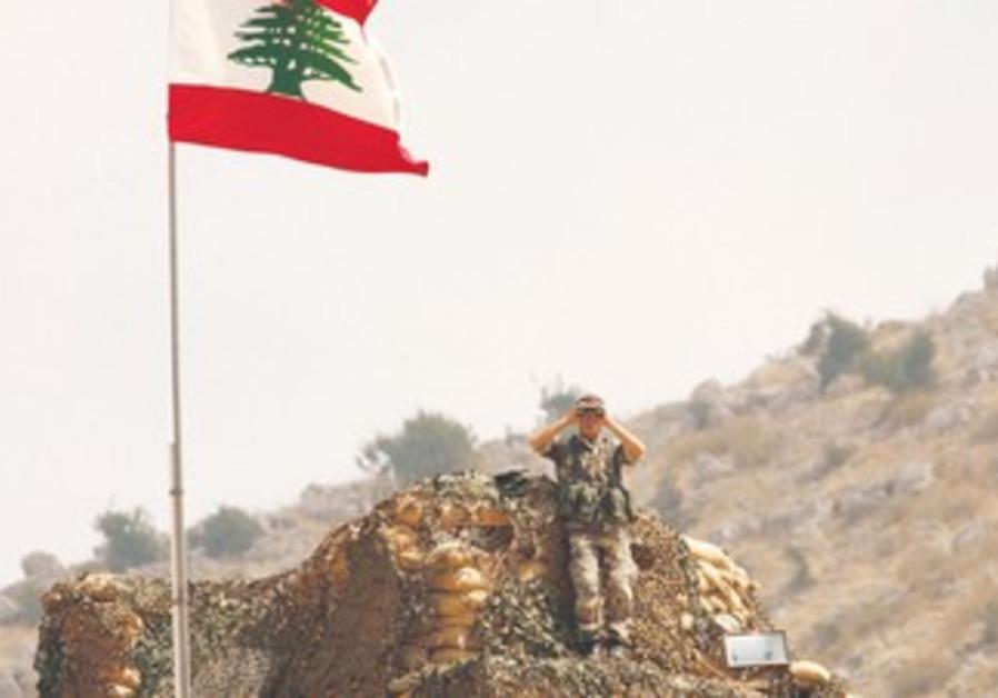 Lebanese soldier peers at Israel along border