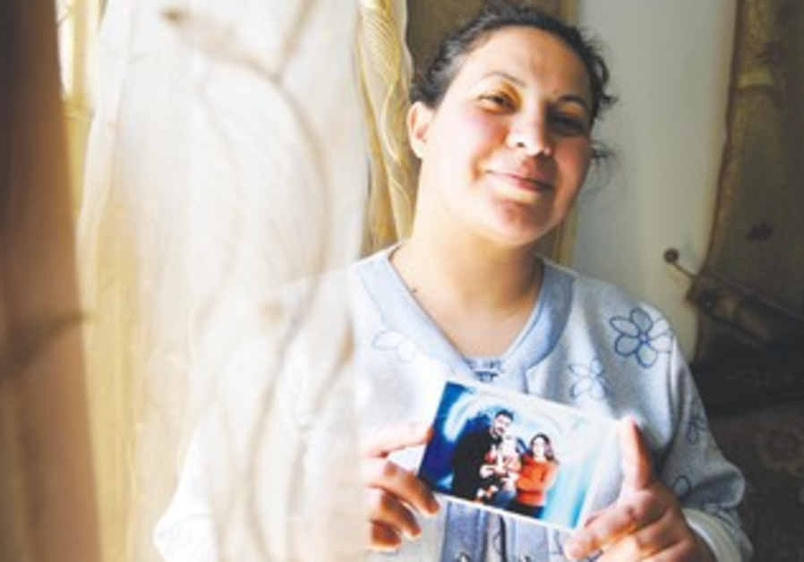 Falastin Jaber holds a photo of her family.