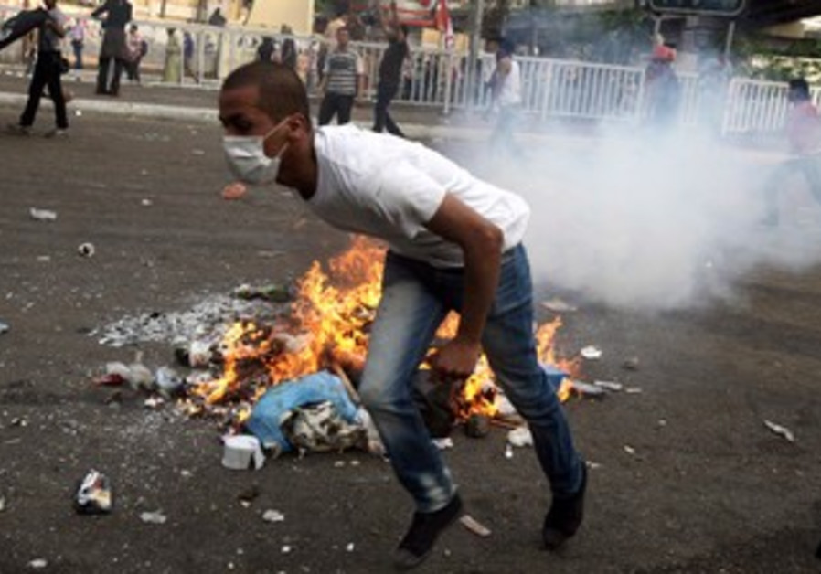 Egypt protester runs from tear gas