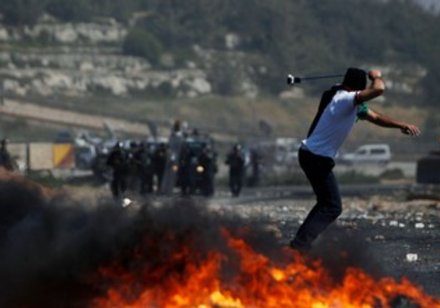 Palestinian throws stone at Beitunia Nakba Day