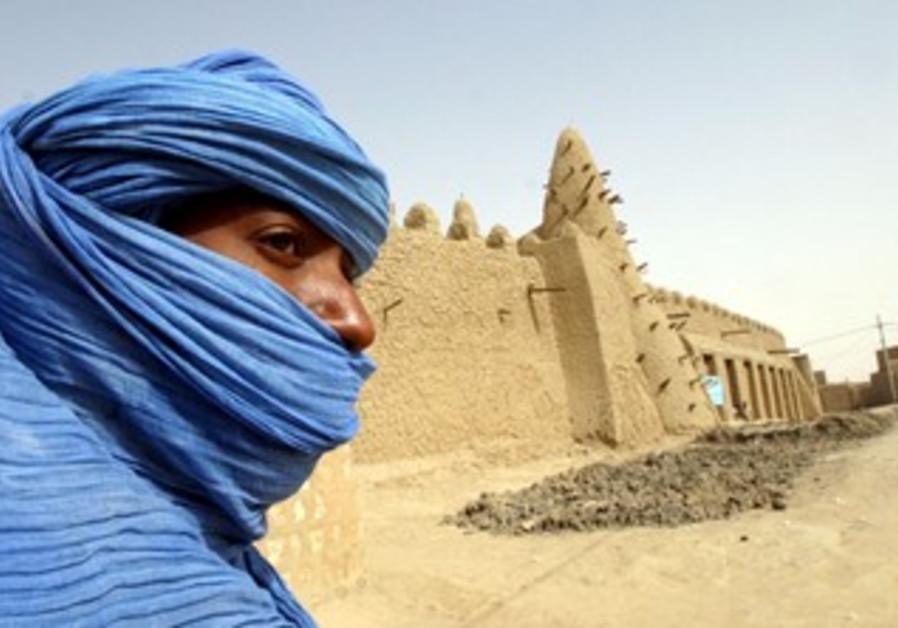 Tuareg nomad stands near 13th century mosque, Mali