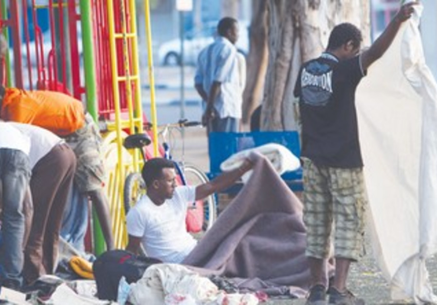 Aftrican migrants pack after night in TA park