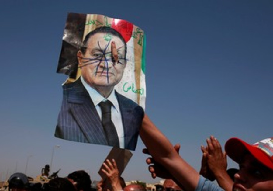 Anti-Mubarak protesters holds defaced picture