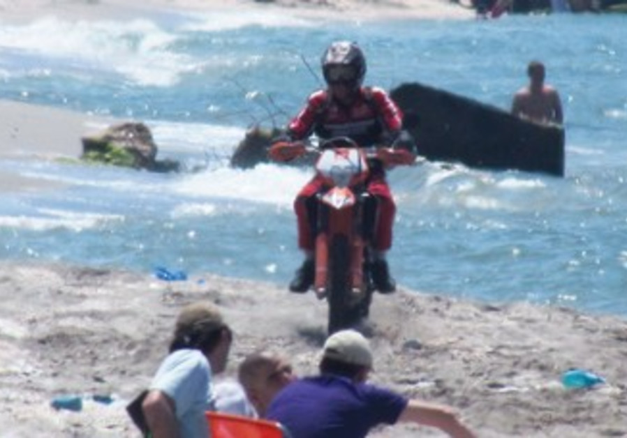 MOTORCYCLIST rides along an Israeli beach